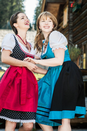german swiss: Two young Woman in traditional austrian Clothes having Fun Stock Photo