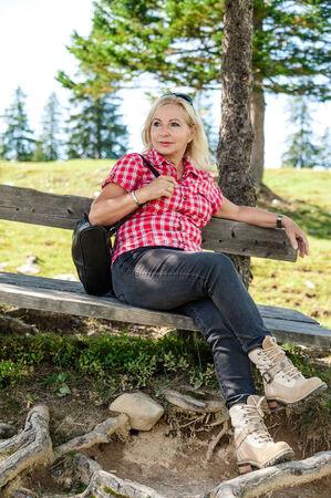 trekker: blonde female hiker take a rest in the austrian alps