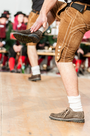 Men dressed in leather trousers is doing the traditional austrian folk dance