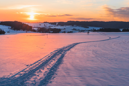 upper austria: Scene with trail on snow at sunset background taken in upper austria Stock Photo