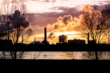 industrialized: Factory with smokestacks at sunset with trees and river in the foreground
