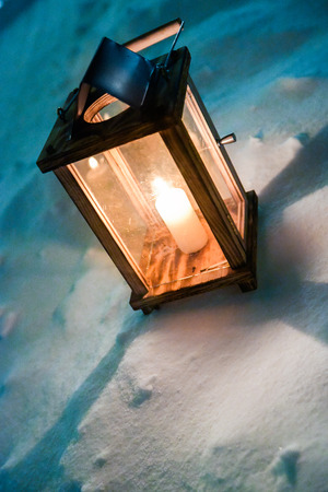 Single candle light lantern standing in snow Imagens