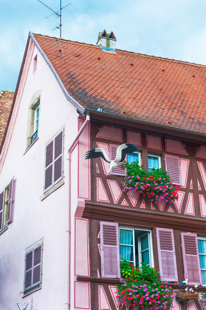 half timbered house: pink half timbered house in alsace decorated with a stork Stock Photo