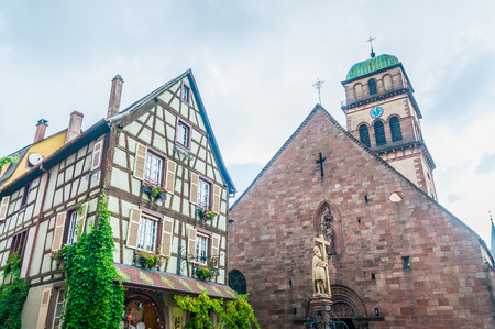 half timbered house: typical church and house in alsace, france