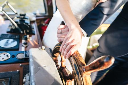 anillos boda: La novia y el novio de la mano y en un volante de madera