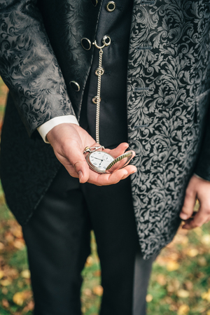 Groom holding an old pocket watch in his hands. Maybe he is waiting for his bride Stock Photo