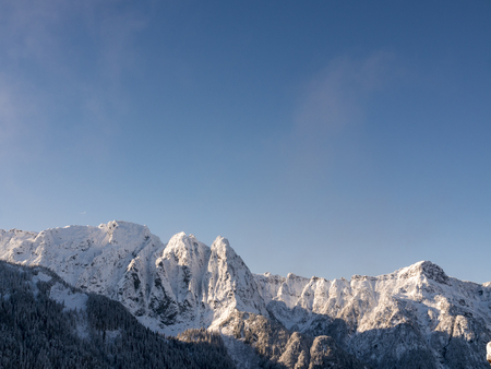 lookout: Blue Sky Nature Background Above Snow Covered Jagged Peaks on Mountain Ridge