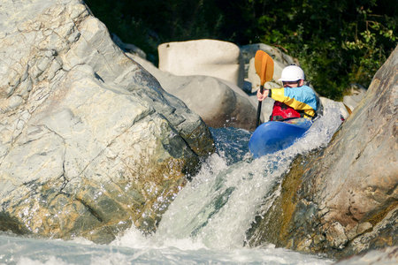 white water: Extreme Kayaker Going Over Rocky Waterfall Drop in Raging River Rapids