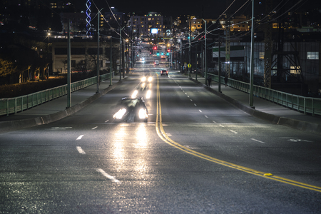 Looking down Jose Rizal Bridge road on dark evening with people commuting home from work 스톡 콘텐츠