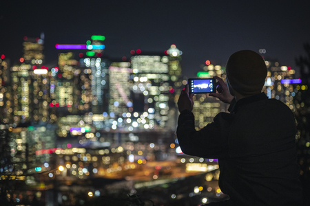 Colorful blurry background from urban buildings at night with man holding cell phone snapping pictures for social media