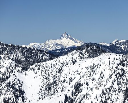 Washington rocky summit covered in white snow on blue sky day