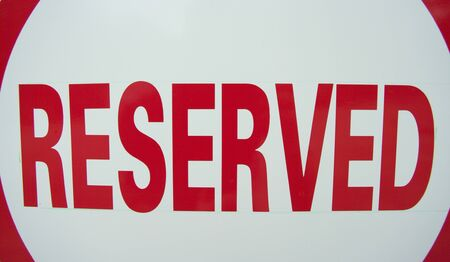 allocated on white: close cropped RESERVED sign. Red lettering on a white background
