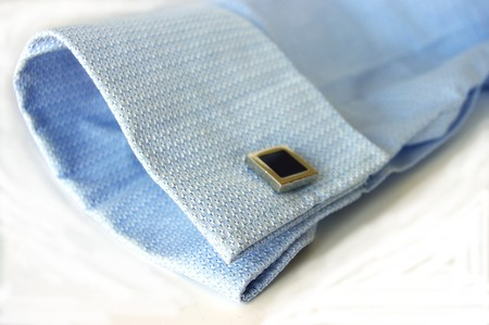 french cuffs: Blue business shirt cuff and square silver cufflink Stock Photo