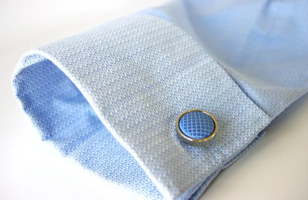 french cuffs: Blue business shirt cuff and round silver cufflink with blue material insert
