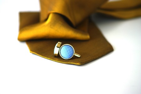 french cuffs: Gold tie and silver cufflinks with blue material inserts Stock Photo