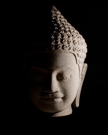 stone buddha: Stone Buddha head. Strong side lighting. Isolated on black. Stock Photo