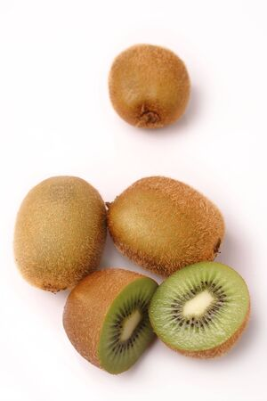 actinidia deliciosa: whole and cross-section of Kiwifruit on a white background. Shallow depth of field.  Stock Photo