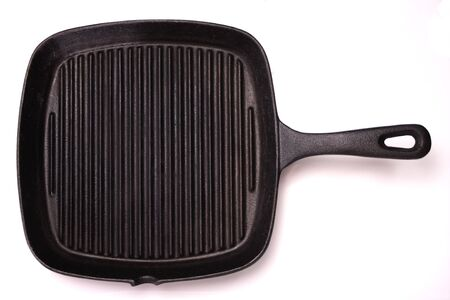 A black, cast-iron grill pan. Isolated on white. photo