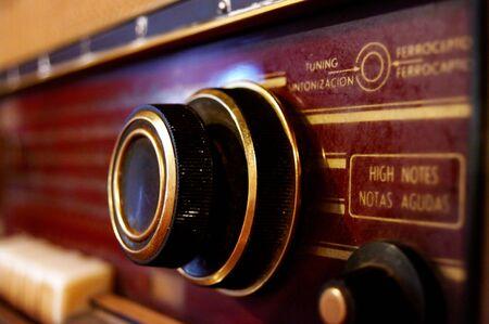 wijzerplaat: Retro antieke radio. Warme tinten, lichte korrel en ondiepe scherptediepte gericht op de tuning wiel.