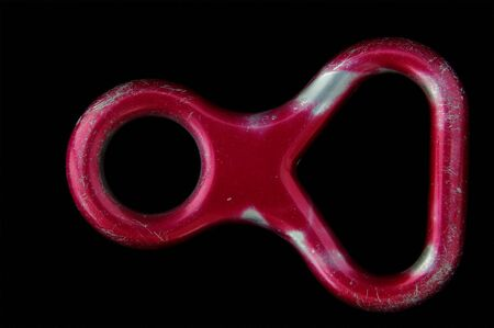 belay: Figure eight descender. Worn from use. Shot on black background Stock Photo