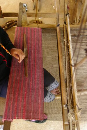 weft: Colorful threads being woven on a hand loom.  Stock Photo
