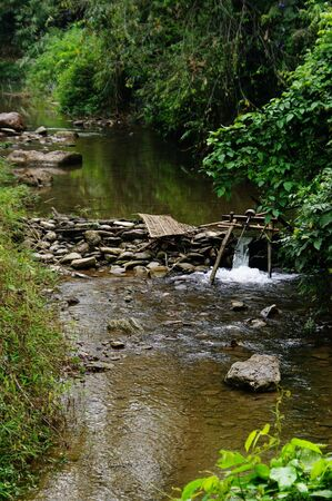 ou: Improvised run-of-stream micro hydro electricity generation. Using boat propellers in rapids driving shafts to electric motors, all supported on bamboo scaffolding. Nam Ou River Tributary, Lao