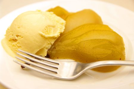 poached: A delicious vanilla bean poached pear and ice-cream dessert. On a plate and ready to eat.