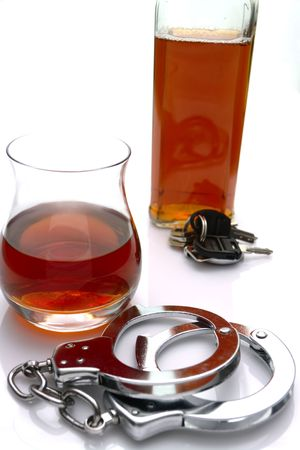sobriety: Conceptual driving under the influence of alcohol shot. High key scene of  handcuffs, alcoholic drinks and car keys
