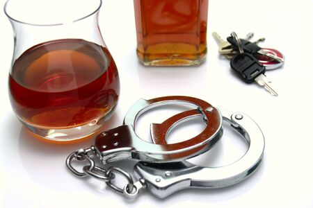 dui: Conceptual driving under the influence of alcohol shot. High key scene of  handcuffs, alcoholic drinks and car keys