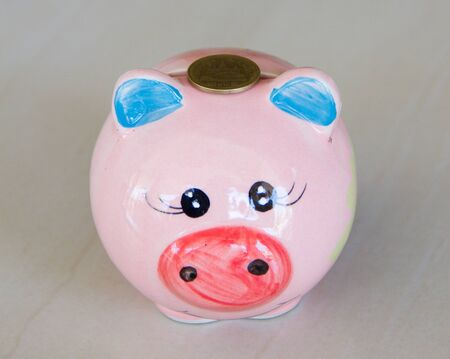 Saving,female hand putting a coin into piggy bank photo
