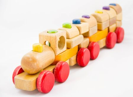 Wooden toy train with colorful blocs on white background photo