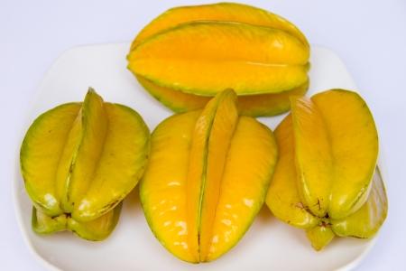 exotic fruits: carambola on white dish and white background