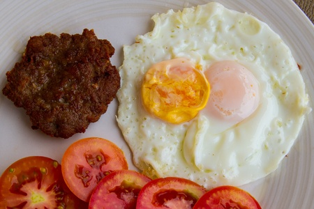 Fried pork with fried two eggs  and tomato photo