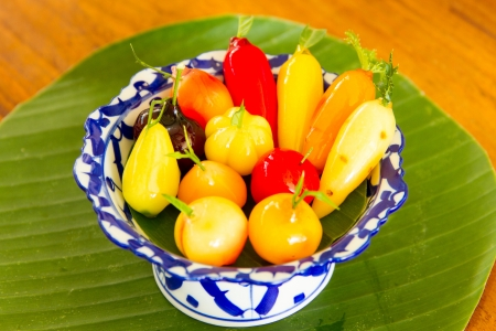 Deletable imitation fruits in dish on banana leaves photo