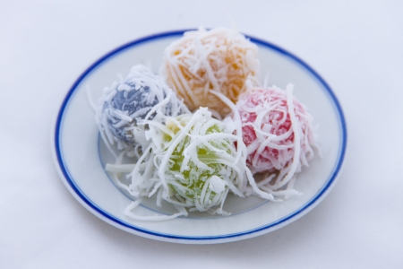Sweet boiled ball dessert, roll over the grated coconut  place on white dish photo