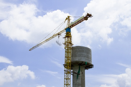 Tower crane and water tank with blue sky and cloud white Editorial