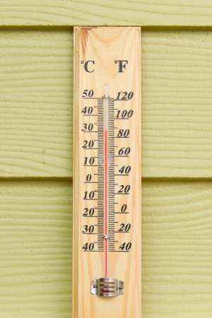 Thermometer mounted on the wall of green wood photo