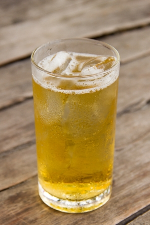 Beer and ice in glass on wooden table photo