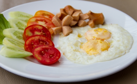 Fried eggs with sausage and and vegetables photo