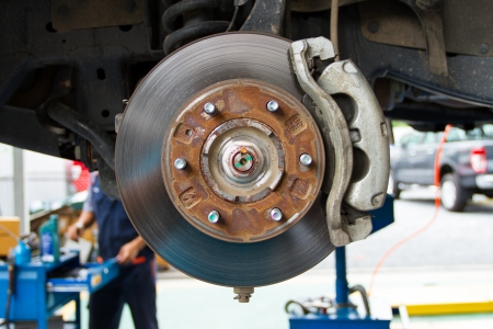 Disc brake and suspension of lifted automobile at repair service station