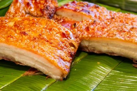 Crispy pork placed on a banana leaf Stock Photo