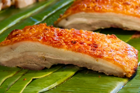 Crispy pork placed on a banana leaf photo