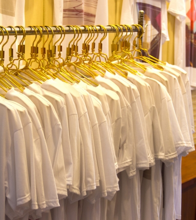 row of white shirts hanging on photo