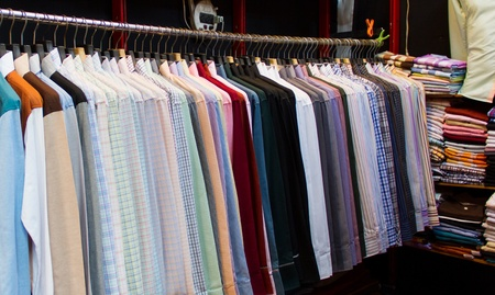 row of colorful  shirts hanging in shop for sale photo