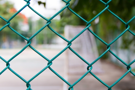 Wire fence with futsal field on background photo