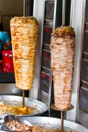 A large piece of   meat cooked in a machine or kebab photo