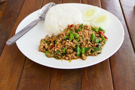 Basil Fried Rice with Pork.Basil fried rice with pork in white dish on wooden table photo