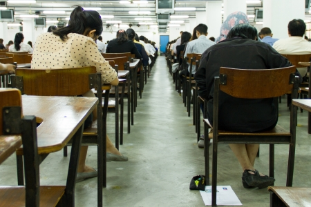 Students sitting in an exam hall doing an exam in university\
