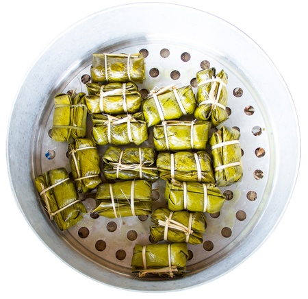 Glutinous rice steamed in banana leaf(Khao Tom Mat or Khao Tom Pad)bananas and sticky rice inside in steam box photo
