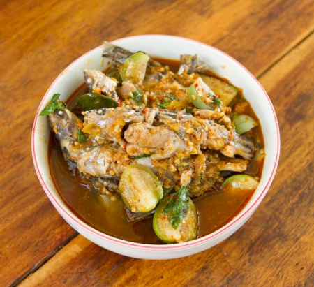 Fish curry with eggplant placed on a wooden table photo